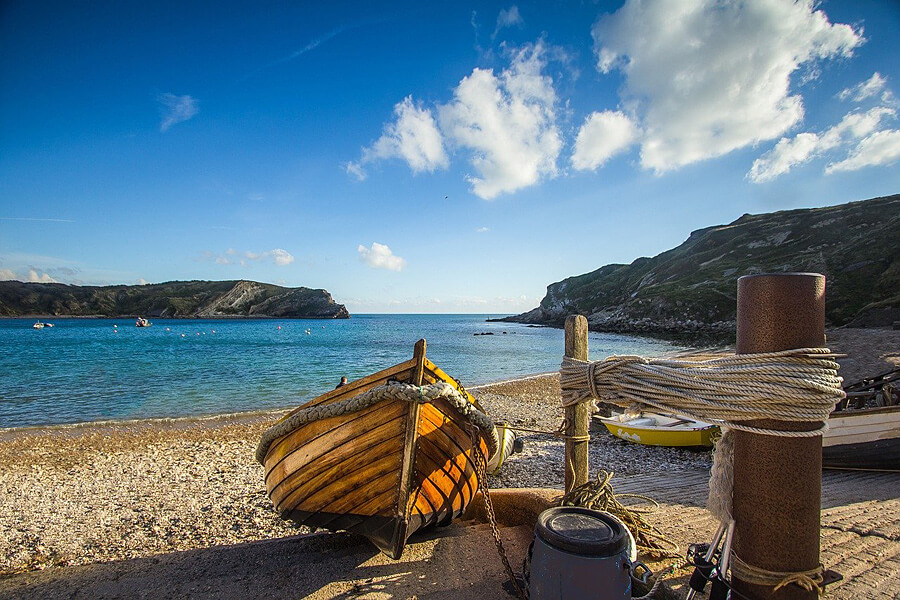 Small fishing boat on a pebbly beach by a beuatiful blue sea
