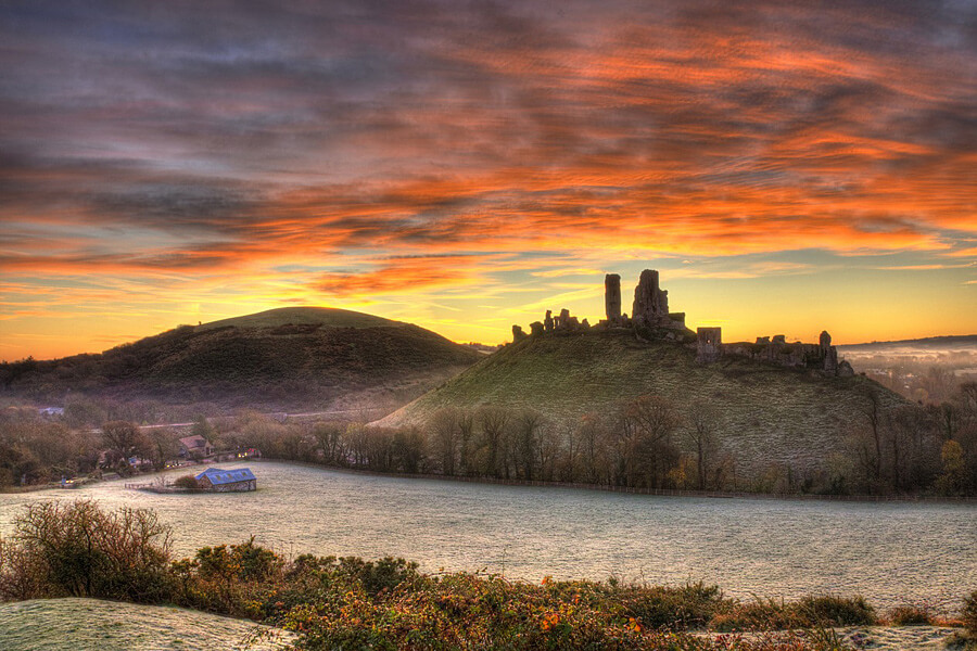 Clouds lit up by a firey sunst over the ruins of Corfe Castle, Dorset